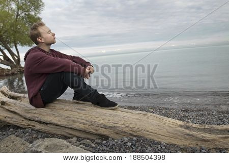 Young man sitting on log beside lake and thinking deeply looking up