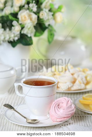 Cup of hot tea with pink homemade zephyr or marshmallow on white table with a bouquet of flowers
