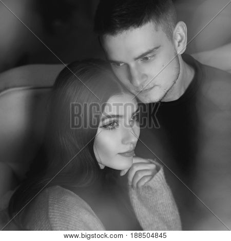 Closeup portrait of young romantic caucasioan couple sitting and higging in christmas decorated interior. Cute lovers staying at home and enjoying tome together