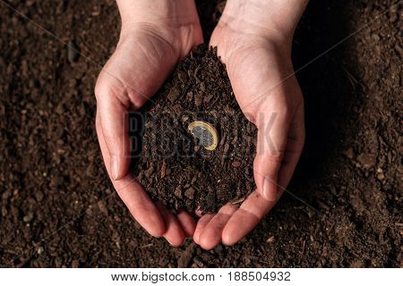 Making income from agricultural activity and earning extra money female farmer handful of soil with euro coin