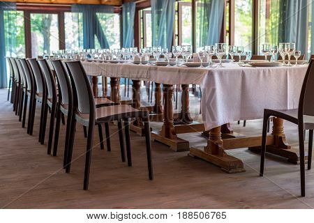 Interior Of The Restaurant, Cafe. Tables With Utensils, Plates, Wiches, Knives, Glasses And Wine Gla