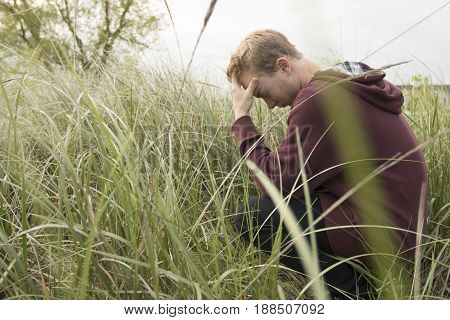 Young man in open filed praying with head down