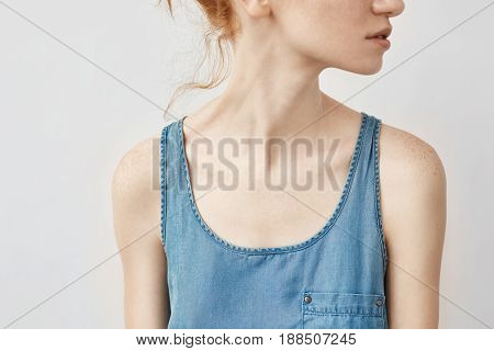 Close up photo of redhead girl in blue shirt looking in profile. Focus on clavicles. Copy space. Isolated on white background.