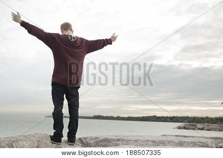 Young man with outstretched arms open wide beside lake