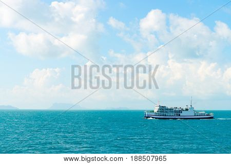 Turquoise calm sea water cloudy sky and white ferry boat with passengers and transport in clean blue sea