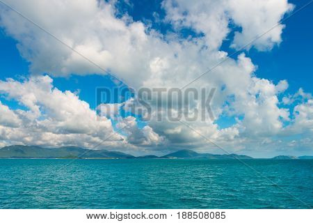 Scenic Of The Tropical Island, Sea Ocean Water, Mountain On Horizon And Cloudy Sky