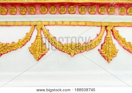 Traditional thai golden pattern floral ornament on a white wall in a temple