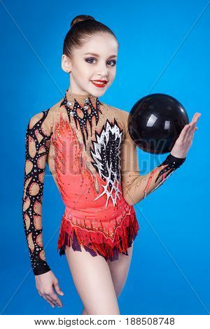 Young caucasian gymnast with a ball on a blue background