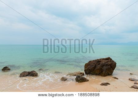 Stones In The Water On The Sandy Beach