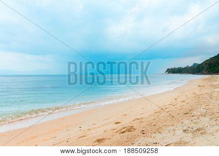 Tropical Rain Clouds On The Calm Sea And Deserted Beach