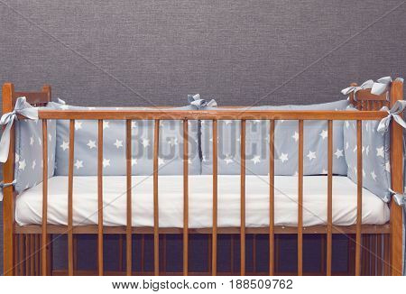Vintage wooden empty baby cot with decorated pillows