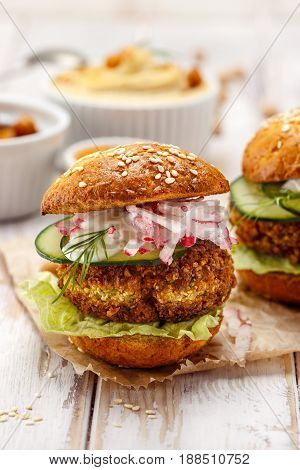 Falafel burger with addition of fresh cucumber, radish and Iceberg lettuce on a wooden rustic table. Healthy and delicious  vegetarian dish