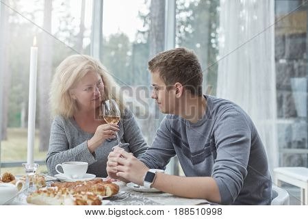 Authentic shot of traditional family sharing experiences of happiness at home and daily life activities. Young hansome male is drinking tea with his mature beautiful mother in a stylish country house. Blond lady is looking at his son with love and drinkin