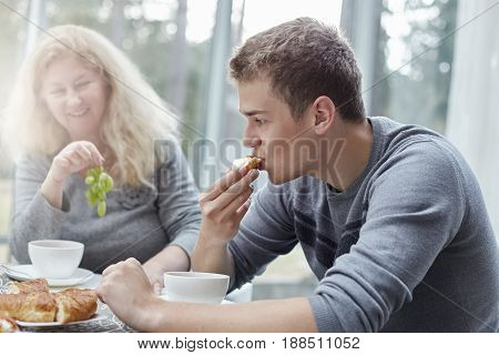 Authentic shot of traditional family sharing experiences of happiness at home and daily life activities. Young hansome male is having breakfast with his mature beautiful mother in a stylish country house.