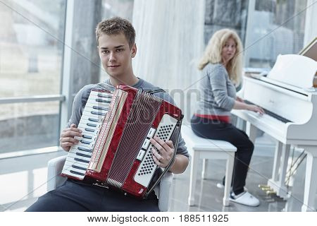 Portrait of young handsome Caucasian blue- eyed male playing accordeon in a luxury house with stylish modern interior. His beautiful mature mother accompanies on the white graceful piano in background.