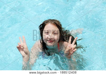 Beautiful young girl 13 years old showing two thumbs up swims in the pool at the spa