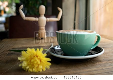 Hot mocha coffee or capuchino with yellow flower and wood man on the wooden table