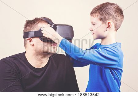 Father and son trying VR glasses at home.