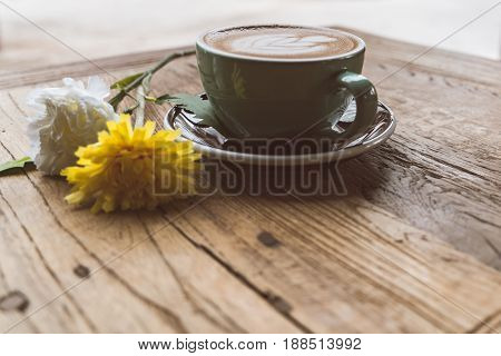 Hot mocha coffee or capuchino with heart pattern and yellow flower on the wooden table