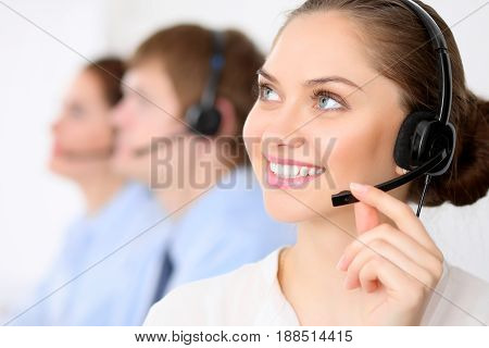 Call center operators. Young beautiful business woman in headset. Call center. Male call operator in headset at the background
