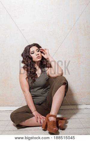 girl in green dress sits on the wooden floor in the room