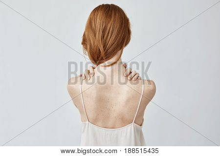 Young redhead girl with freckles posing back to camera with hands on shoulders. Copy space. Isolated on white background.