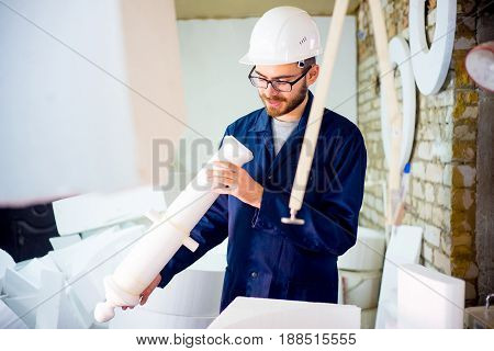 A portrait of a modern factory personnel. Worker cuts polystyrene foam
