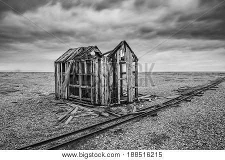 Derelict Fishing Hut And Rails On Shingle Beach During Stormy Winter Landscape