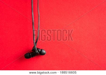 Old back earbuds and red background. In Closeup.