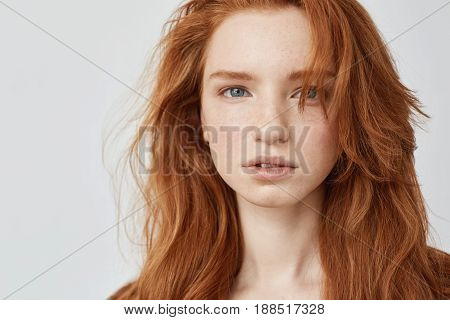 Close up photo of beautiful natural redhead model with freckles looking at camera. Copy space. Isolated on white background.
