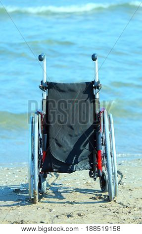 Wheelchair On The Shore By The Sea On A Hot Sunny Summer Day