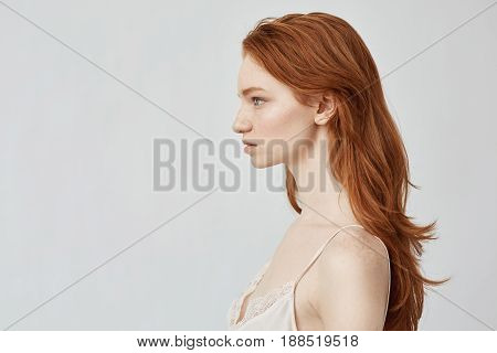 Portrait of young tender beautiful redhead girl posing in profile. Copy space. Isolated on white background.
