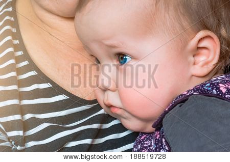 The Child Looks Away From Her Grandmother's Chest.