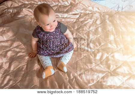 A Child Is Sitting On The Bed And Smiling.