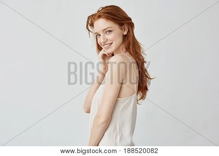 Young beautiful redhead girl with freckles smiling looking at camera. Copy space. Isolated on white background.