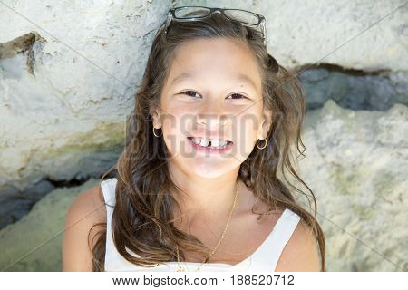 Little Tan Girl Outdoor With Glasses On Shoulder