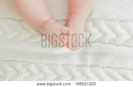 Newborn Baby legs on the bed close-up against a light fabric background