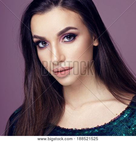 Closeup beauty studio fashion portrait of young pretty girl with long brunette dark hair and nakeup posing in shiny green dress with sequins posing against purple background and looking in camera.