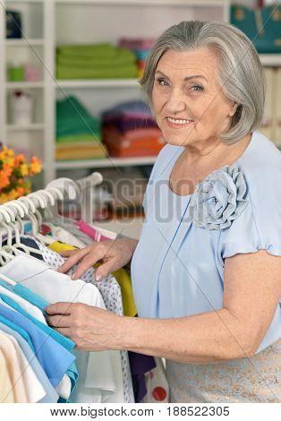 Portrait of a senior woman choosing shirt in shop