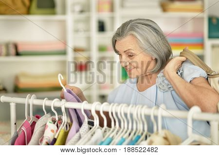 Portrait of a senior woman choosing shirt in shop