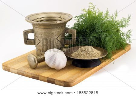 Still Life Spices, Blue Fenugreek , marigold staminas in a copper vase on a wooden board on a background of a stern stupa for grinding spices, bunches of dill and garlic