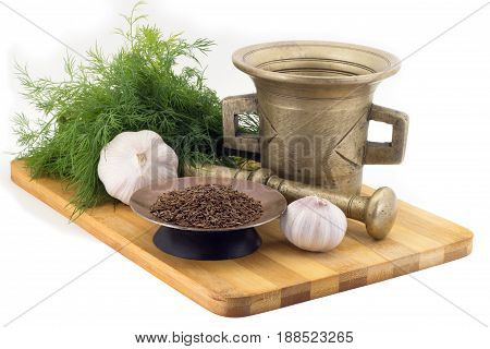 Still Life Spices, Cumin , marigold staminas in a copper vase on a wooden board on a background of a stern stupa for grinding spices, bunches of dill and garlic