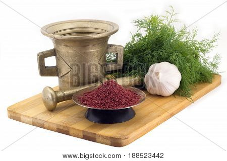 Still Life Spices, Beetroot spice for vegan soups , marigold staminas in a copper vase on a wooden board on a background of a stern stupa for grinding spices, bunches of dill and garlic