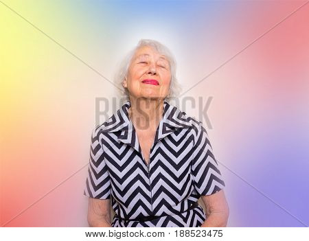 Portrait of a dreaming senior woman sitting with closed eyes. Over colored background.
