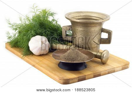 Still Life Spices, cracked black pepper , marigold staminas in a copper vase on a wooden board on a background of a stern stupa for grinding spices, bunches of dill and garlic