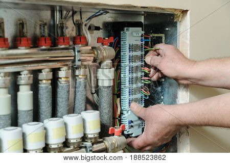 Electrician's hands are inserting wires in a switch for thermostats and servo drives valves in a home heating system.