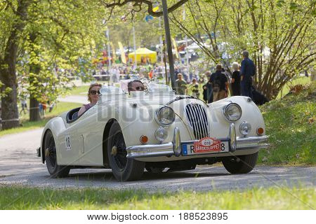 STOCKHOLM SWEDEN - MAY 22 2017: White Jaguar XK 140 MC classic car from 1956 driving on a country road in the public race Gardesloppet in the forests at Djurgarden Stockholm Sweden. May 22 2017