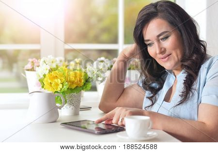 Elderly woman with a tablet on the window background