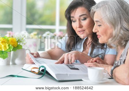 Two elderly girlfriends are reading a book at a table