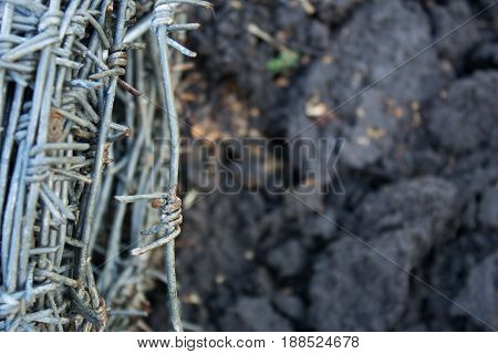 A barbed wire reel on a gloomy ground background. Restricting liberty is a prison or the protection of one's property.